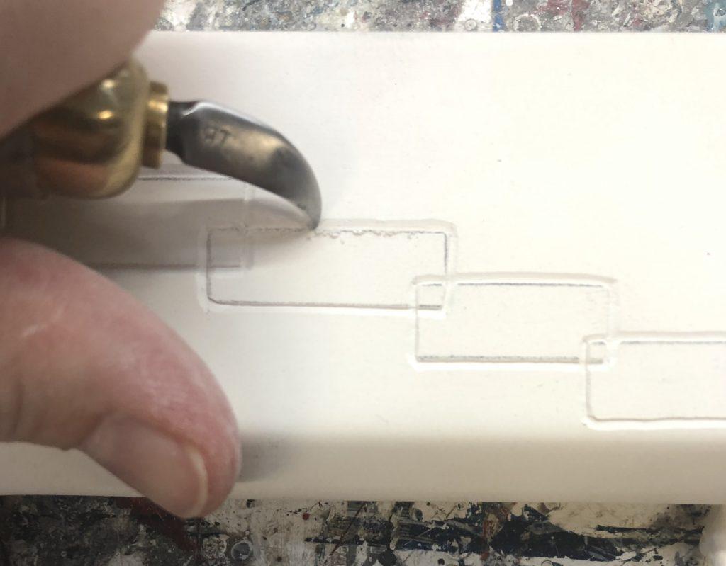 Einblick in die Vergolderwerkstatt der Galerie Tobien, Husum: Detailaufnahme: hier wird gerade ein Modellrahmen graviert. Der Gravurhaken schneidet sauber in den extra dafür vorbereiteten Kreidegrund.
