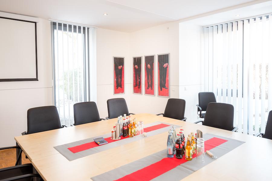 Foto eines Büro bzw. Besprechungsraumes, mit Bildern von Christoph Pöggeler an der Wand: Roter Teppich, Lithografie, handsigniert und nummeriert, Auflage: 40, 100 x 132 cm